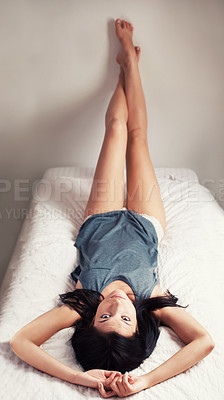Buy stock photo A beautiful young brunette woman lying on her back on a bed