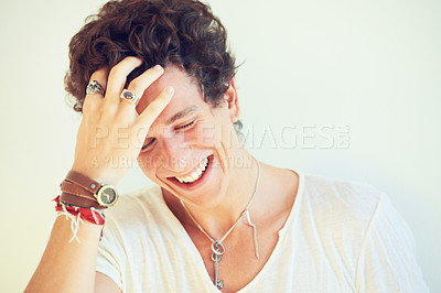 Buy stock photo Portrait of a young man laughing and running his hand through his hair
