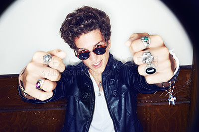 Buy stock photo Portrait of a stylish young man with both ring-clad fists pointed at the camera
