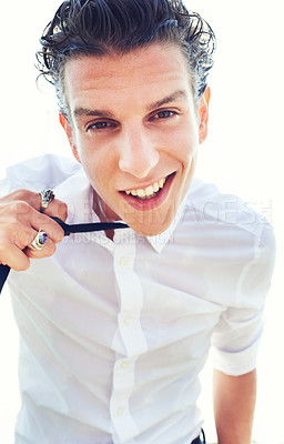 Buy stock photo Low angle portrait of a handsome and stylish young man loosening his necktie
