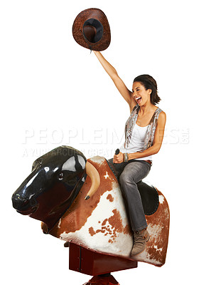Buy stock photo Studio shot of a beautiful young woman riding a mechanical bull against a white background