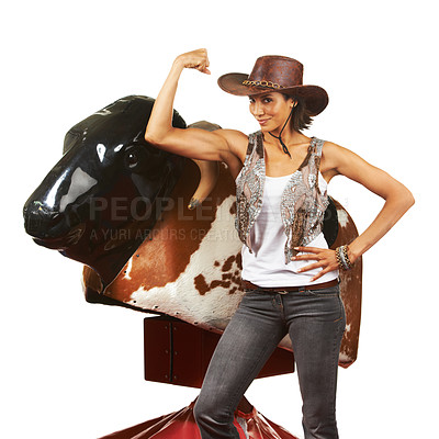 Buy stock photo Studio shot of a beautiful young cowgirl standing next to a mechanical bull against a white background