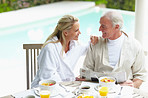 Mature couple having a chat at breakfast table by swimming pool