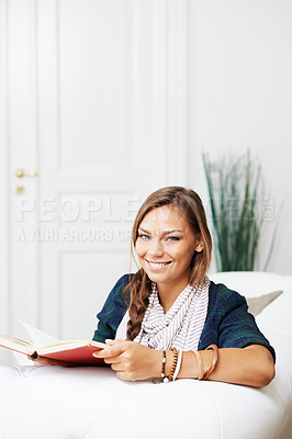 Buy stock photo A young woman reading on her sofa