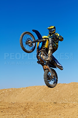 Buy stock photo Action shot of a dirt biker jumping