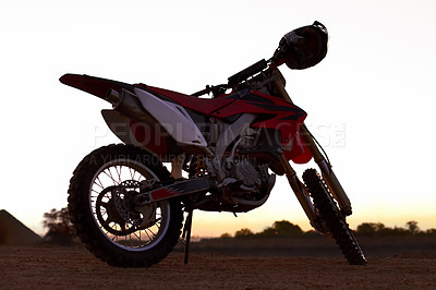 Buy stock photo A dirt bike parked on an open plane with the sun setting in the background