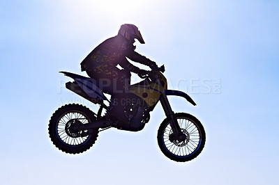 Buy stock photo Silhouette of a biker jumping against a blue sky