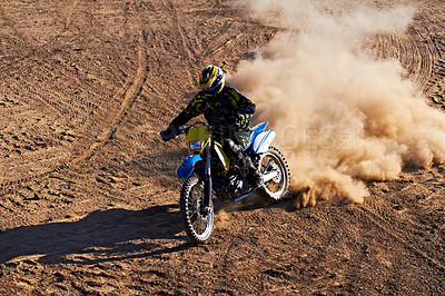 Buy stock photo A dirt biker riding along a track with a cloud of dust following him