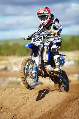 Buy stock photo A motocross rider doing a small jump