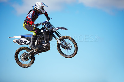Buy stock photo A motocross rider mid-air against a blue sky