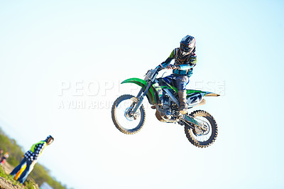 Buy stock photo A motocross racer in mid-air with a spectator looking on in the background