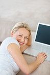 Cute mature lady working on laptop at home