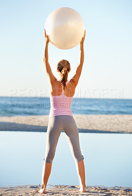 Buy stock photo Rear view of a fit young woman holding a pilates ball above her head at the beach