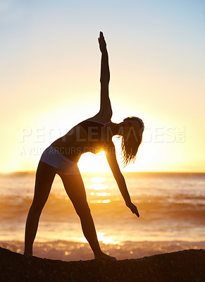 Buy stock photo Silhouette of a young woman doing yoga at the beach