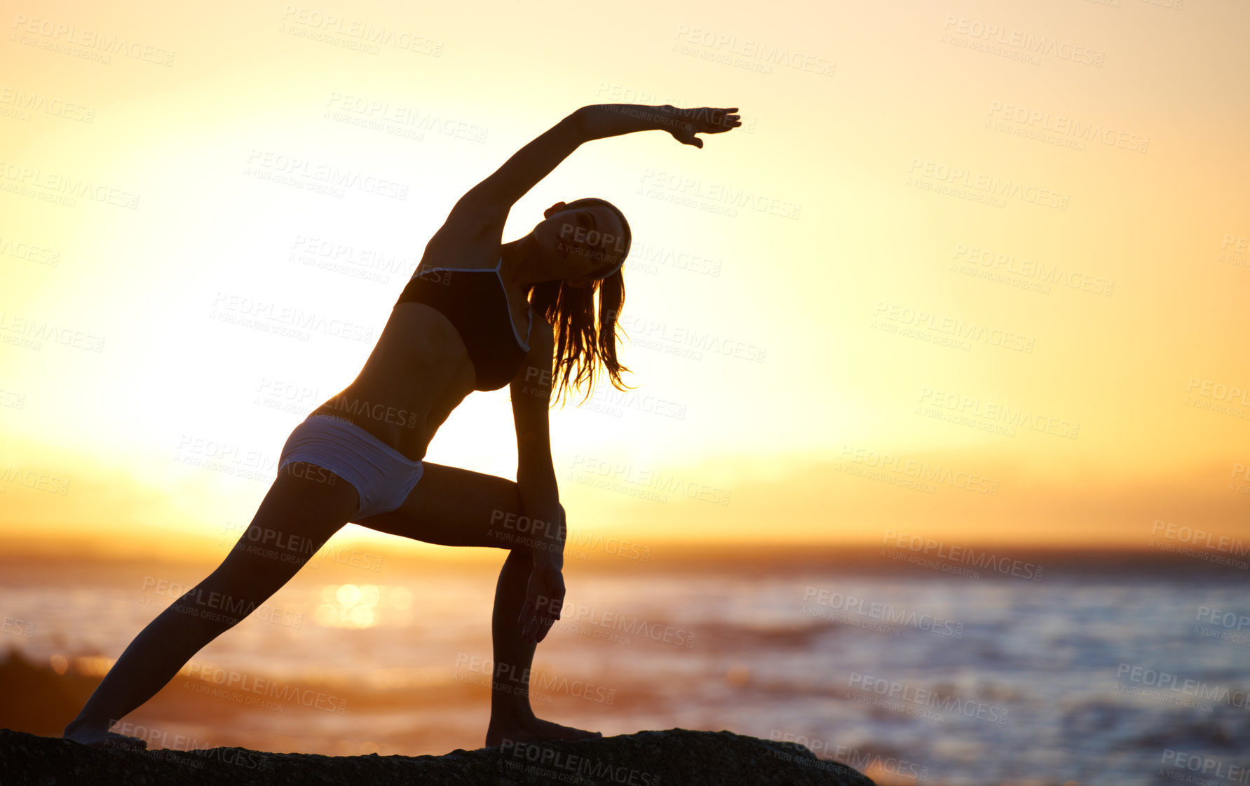 Buy stock photo Silhouette of a young woman stretching on the beach at sunset