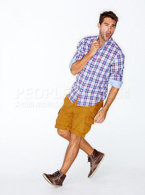 Buy stock photo Handsome young guy stepping out on a white background while holding his collar and shouting