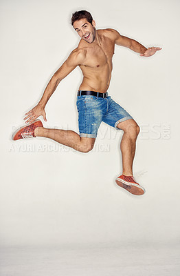 Buy stock photo Muscular young guy jumping in denim shorts while against a white background
