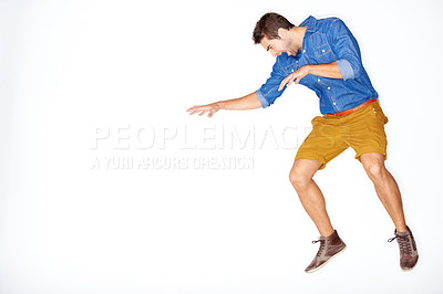 Buy stock photo Stylish young guy jumping expressively against a white background