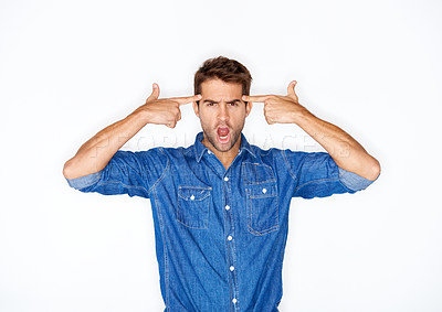 Buy stock photo Handsome young man putting his fingers to his head in a gun gesture