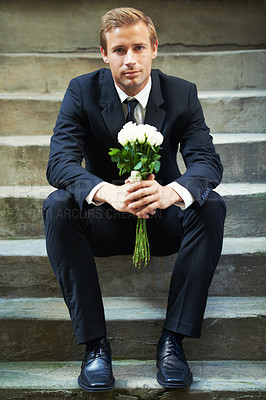 Buy stock photo A handsome man wearing a suit and sitting on stairs holding a bunch of white roses