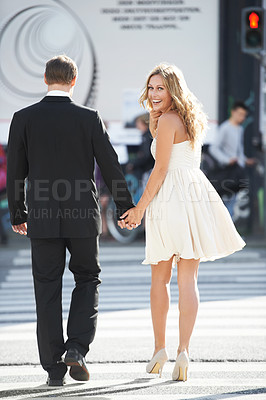 Buy stock photo A beautiful woman glances back and smiles as she crosses the street with her boyfriend