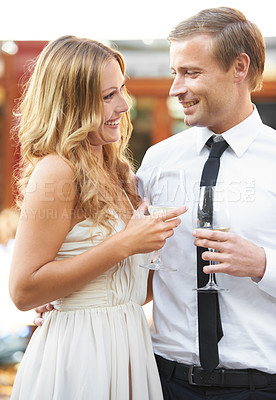 Buy stock photo A beautiful couple stand arm in arm and drink wine in a restaurant