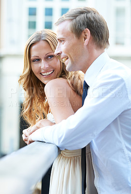 Buy stock photo A beautiful couple stand at a bridge and enjoy each other's company