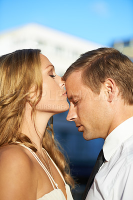Buy stock photo A beautiful woman kisses the forehead of her handsome boyfriend