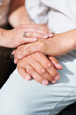 Buy stock photo Cropped shot of a senior couple's hands resting on one another with their wedding rings showing