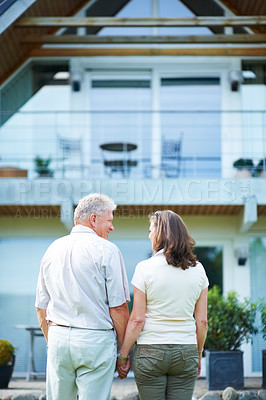 Buy stock photo Rearview shot of a mature couple standing hand-in-hand in front of their home