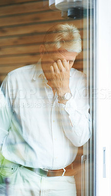 Buy stock photo Cropped shot of a senior man looking stressed while standing at his bedroom window