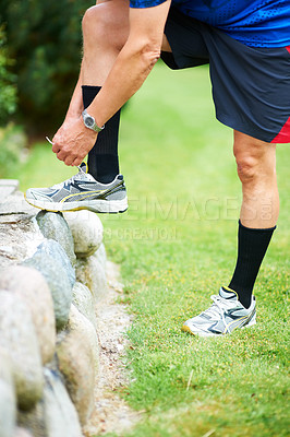 Buy stock photo Cropped shot of a jogger resting his foot on a rock while tying his shoelace