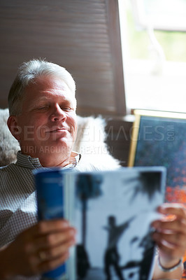 Buy stock photo Cropped shot of a senior man reading a magazine in his bedroom