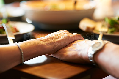 Buy stock photo Cropped shot of a couple holding hands in prayer at the table before eating
