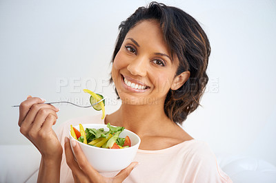 Buy stock photo Portrait of a young woman enjoying a salad at home