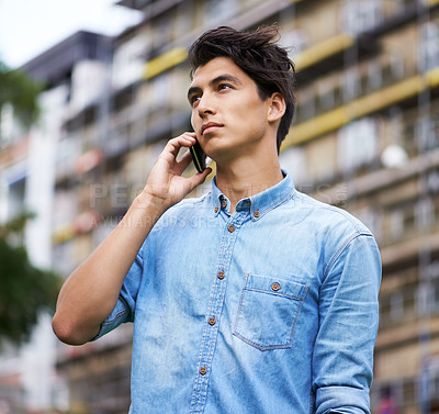 Buy stock photo A handsome young man making a call on his cellphone