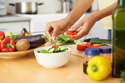 Buy stock photo Cropped shot of a young woman preparing a salad in a kitchen