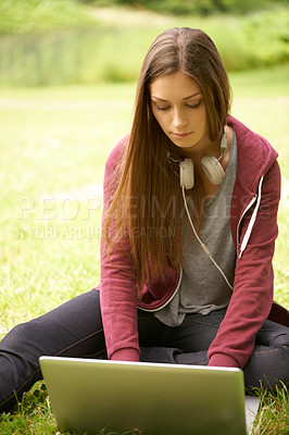 Buy stock photo A lovely young woman working on her laptop outdoors