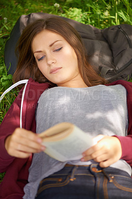 Buy stock photo A lovely young woman reading a book while lying in a field of grass