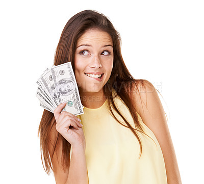 Buy stock photo Studio shot of a young woman holding up fanned out banknotes and thinking about what to do isolated on white