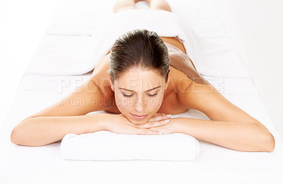 Buy stock photo Studio shot of a young woman lying on a massage bed