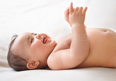 Buy stock photo Profile shot of a cute baby laughing while lying on a bed