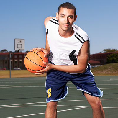 Buy stock photo A young basketball player prepares to dribble a ball