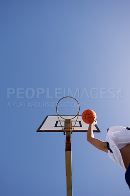 Buy stock photo Low angle shot of a basketball player scoring