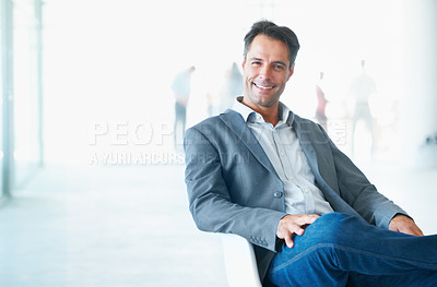 Buy stock photo A mature smiling businessman sitting in his office chair with colleagues blurred in the bright background