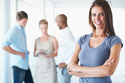 Buy stock photo A young businesswoman posing confidently with her colleagues blurred in the background
