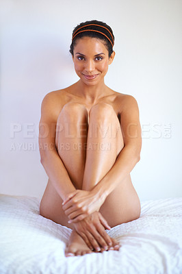 Buy stock photo A gorgeous young nude woman sitting on her bed
