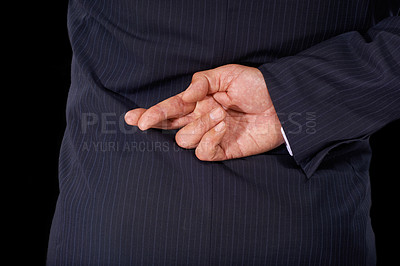 Buy stock photo Cropped view of a man in a suit wth his fingers crossed behind his back