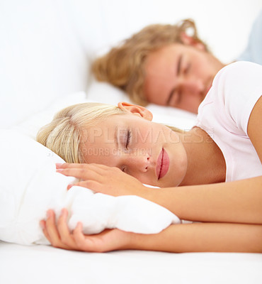 Buy stock photo A young couple asleep in bed together