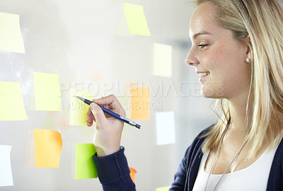 Buy stock photo Profile of a lovely blonde writing on a post-it stuck to a transparent wall - copyspace